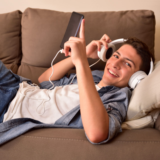 """""""Teen lying face up on couch consuming multimedia front view"""" stock image"""