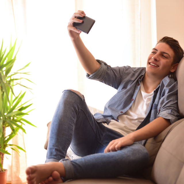 """""""Teen taking a selfie sitting on a couch in the living room"""" stock image"""