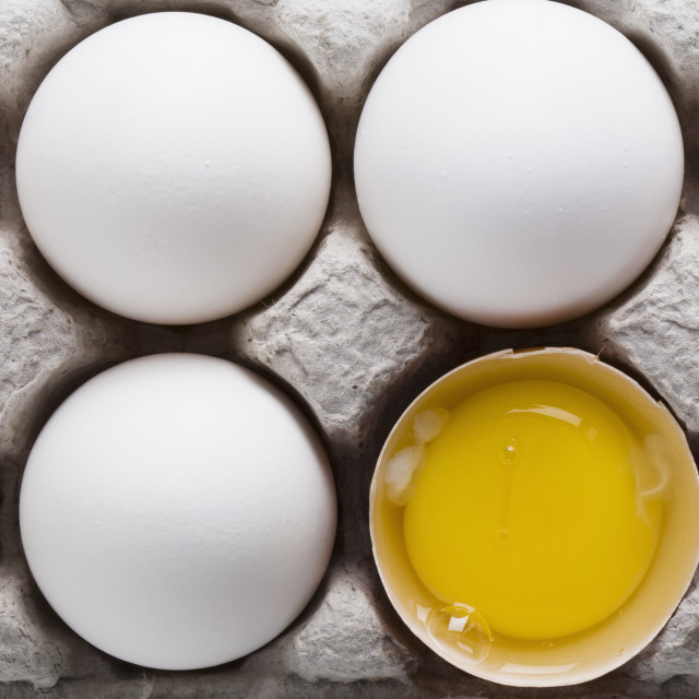 """""""White Eggs In A A Carton With One Brown Shelled Egg Open Showing The Yoke;..."""" stock image"""