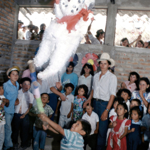 """A boy hits a piñata doll, at a birthday party, in a refugee camp, in El..."" stock image"