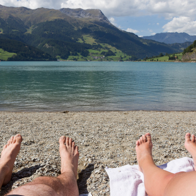 """Feet on the beach, relaxing at the Reschensee"" stock image"