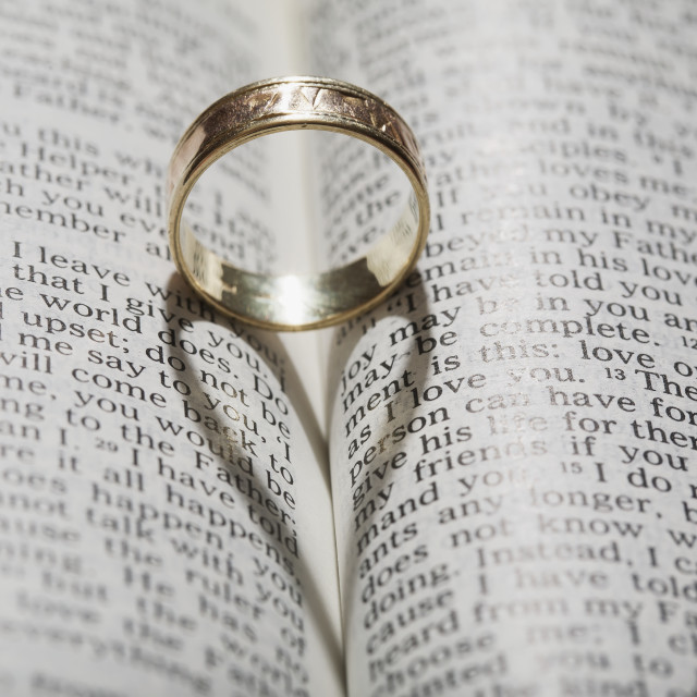 """""""Close up of a gold ring with the shadow of an heart on book about..."""" stock image"""