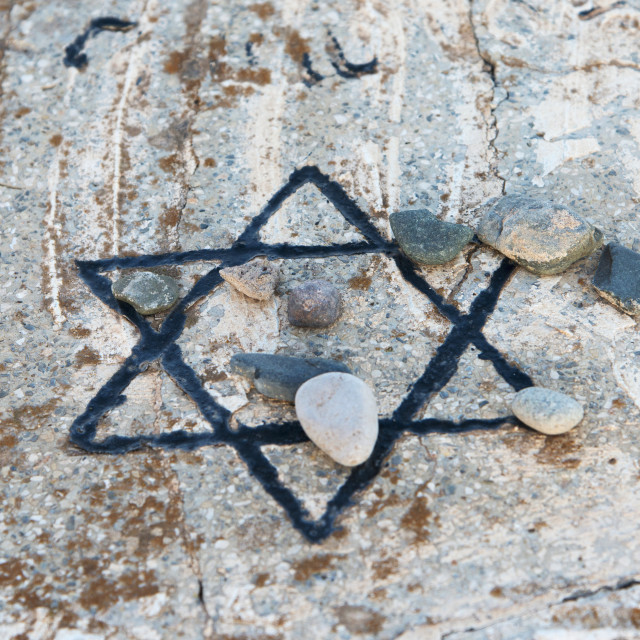 """""""A star of david etched and painted on a rock with stones laying on it"""" stock image"""