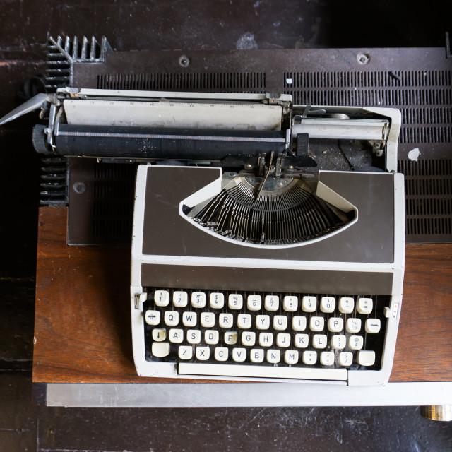 """""""Vintage typewriter on a vintage desk with natural light."""" stock image"""