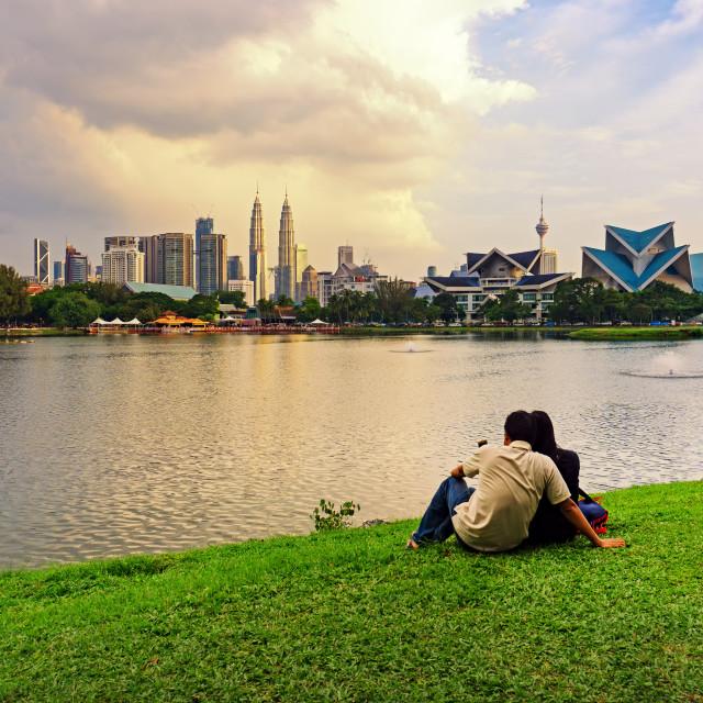 """Unidentified couple at Taman Tasik Titiwangsa during sunset with Kuala Lumpur skyline, Kuala Lumpur, Malaysia."" stock image"