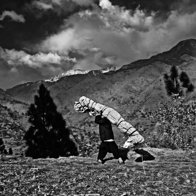 """After the devastation of the 2005 Kashmir earthquake, a man carries a tent up..."" stock image"