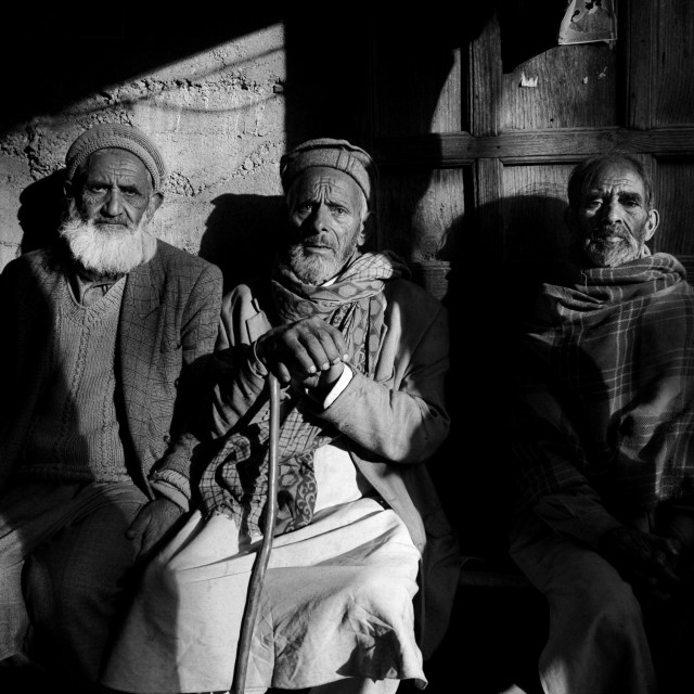 """Muhammad Fareed, a shopkeeper, chatting with his friends in his shop at..."" stock image"