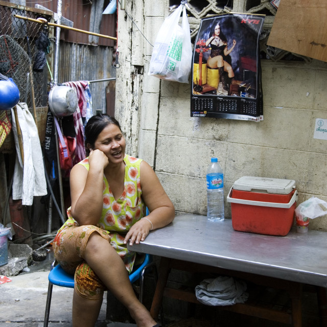 """Woman and pin up poster in Bangkok back street. Thailand, January 18, 2007."" stock image"