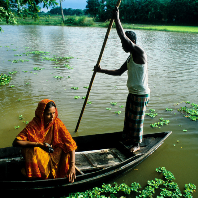 """Fatema Begum and her husband, Badruddin Zaman, cross a flood zone to visit a..."" stock image"