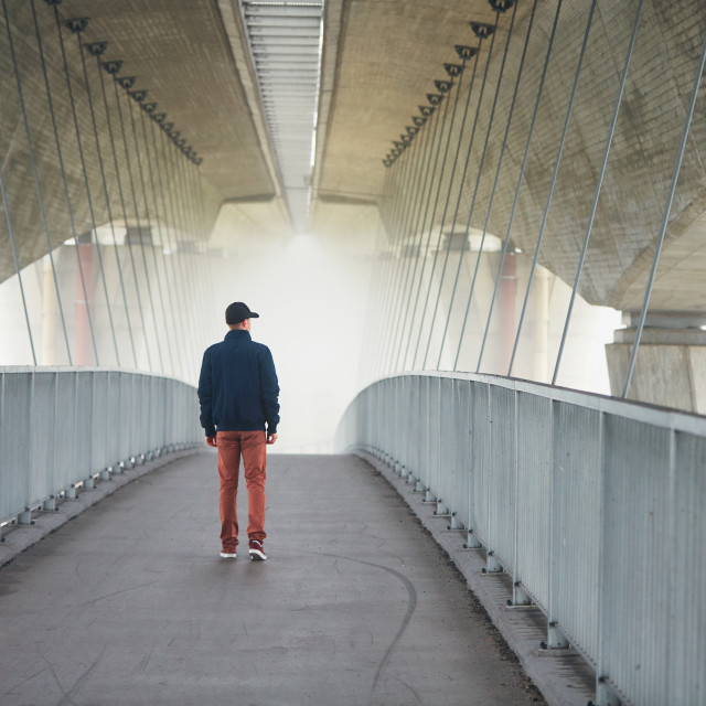 """Man under highway brige in mysterious morning fog"" stock image"
