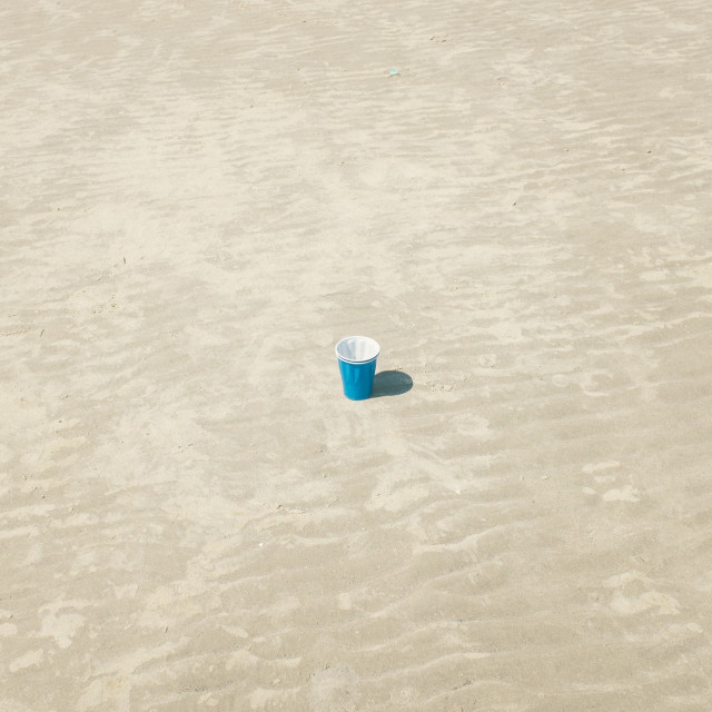 """A Blue Solo Cup Sitting in the Sand"" stock image"