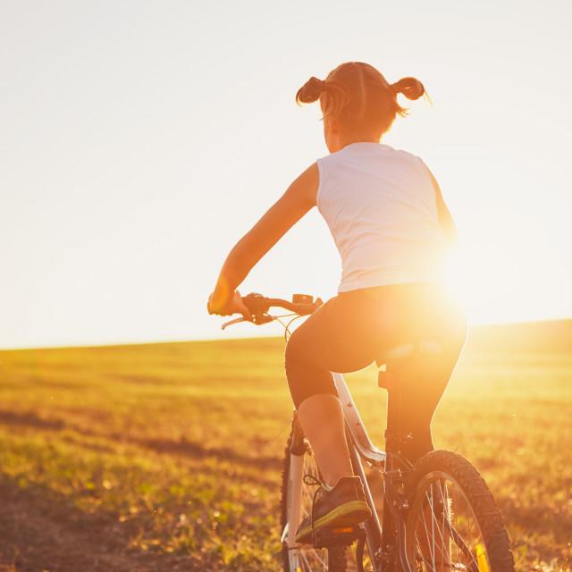 """Girl enjoying bike ride at the sunset"" stock image"