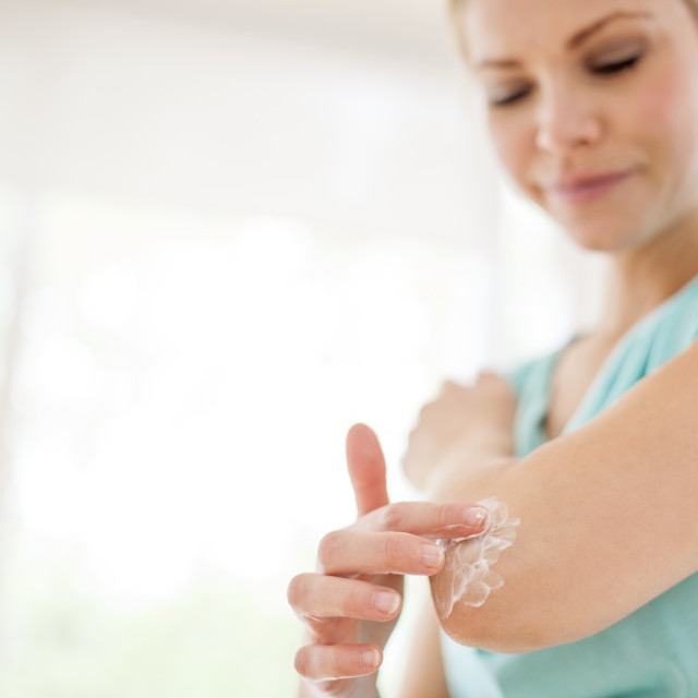 """Woman applying body lotion"" stock image"