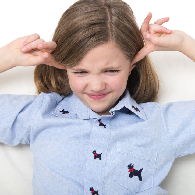 """Girl with her fingers in ears"" stock image"
