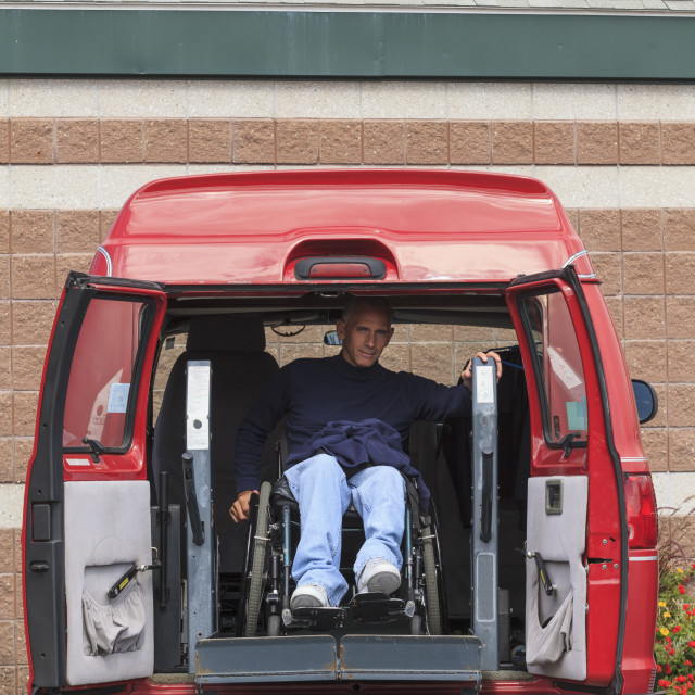 """Man with disability exiting from his van"" stock image"