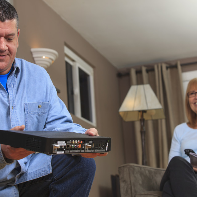 """""""Service man installing a cable box"""" stock image"""