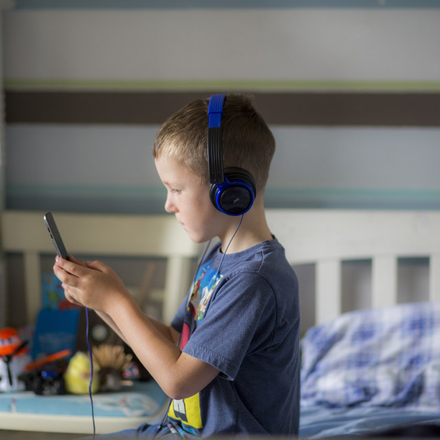 """Boy wearing headphones using device"" stock image"