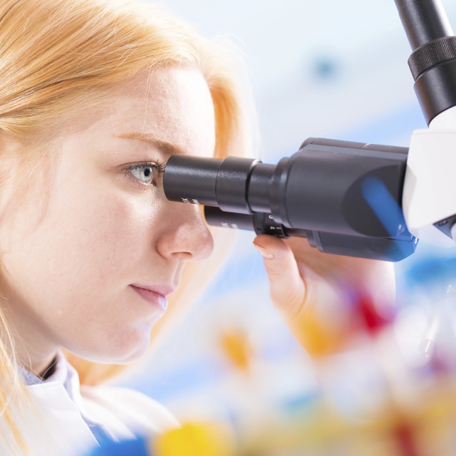 """Lab technician using microscope"" stock image"
