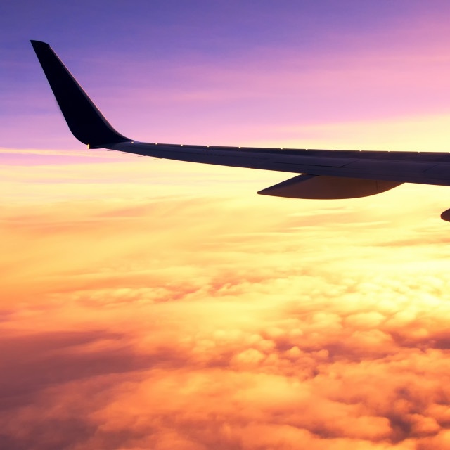 """Airplane wing with dramatic and colorful sunrise"" stock image"