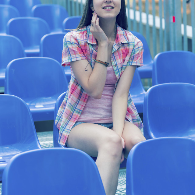"""""""Young woman sitting on blue plastic seat"""" stock image"""