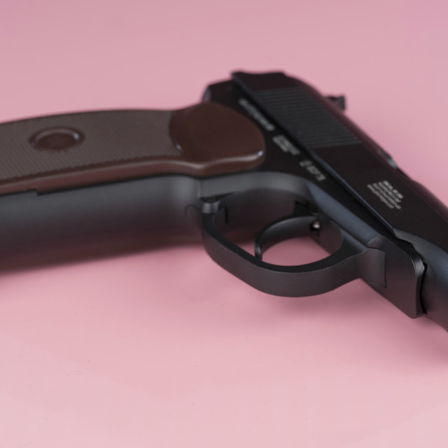 """Handgun against a pink background"" stock image"