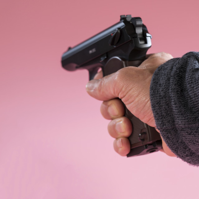 """Person holding handgun against a pink background"" stock image"