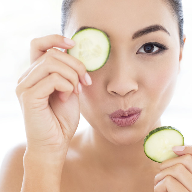 """""""Woman holding cucumber in front of eye"""" stock image"""