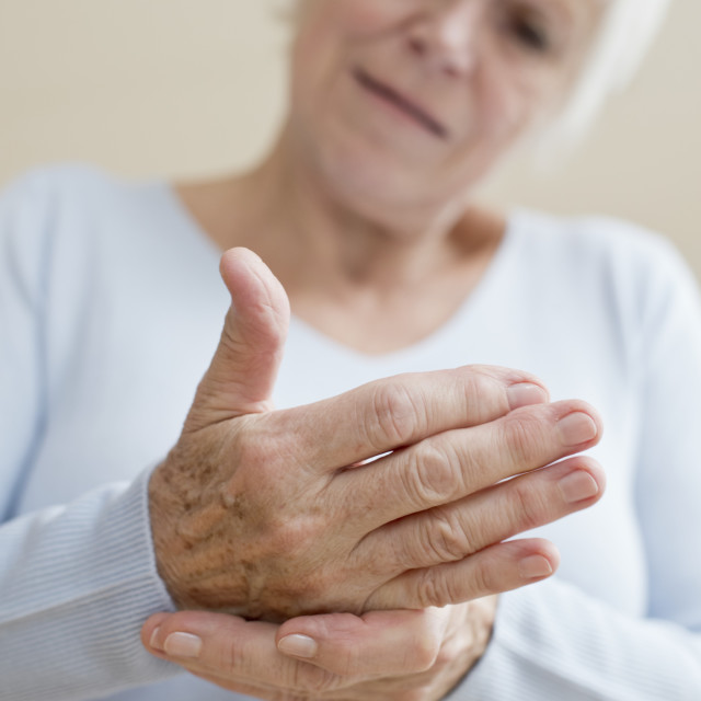 """Senior woman touching sore hand"" stock image"