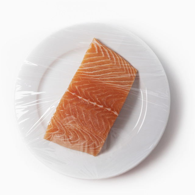 """Salmon On A Plate With Plastic Wrap"" stock image"