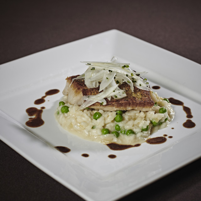 """""""Plated Dinner Of Artichoke Topped Fish Steak With Risotto And Peas Drizzled..."""" stock image"""
