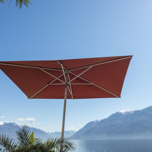 """A Patio Umbrella And Lamp Post Against A Blue Sky With A View Of Lake..."" stock image"