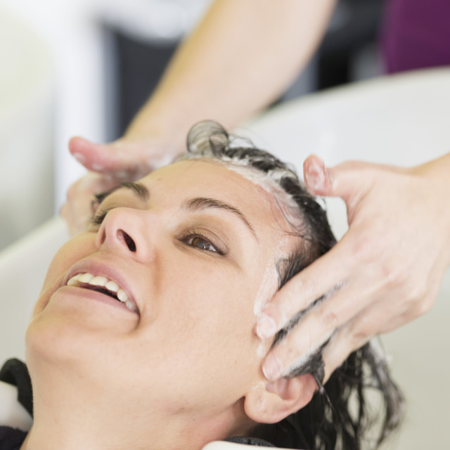 """""""A Woman Getting Her Hair Washed In A Salon Sink; Locarno, Ticino, Switzerland"""" stock image"""