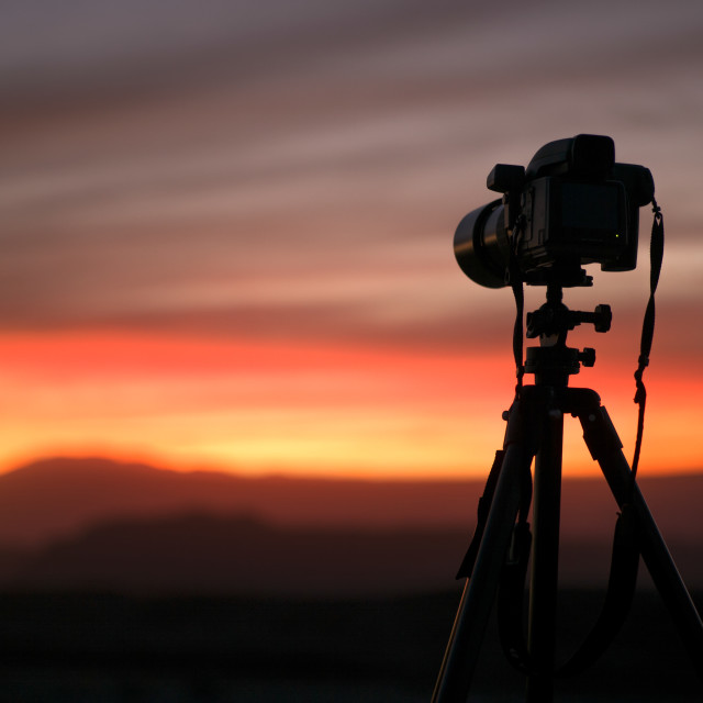 """""""A Camera Set On A Tripod Aimed At A Silhouette Of A Landscape At Sunset; San..."""" stock image"""