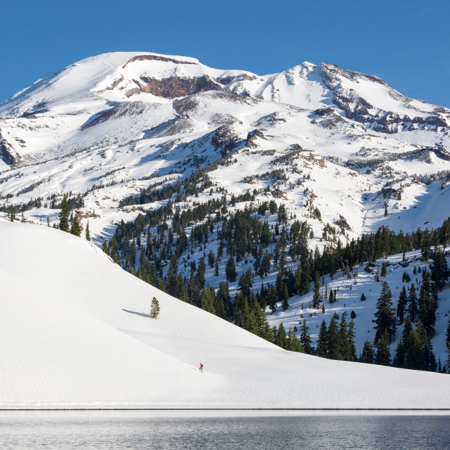 """Snowy Hiker at Mountain Lake"" stock image"