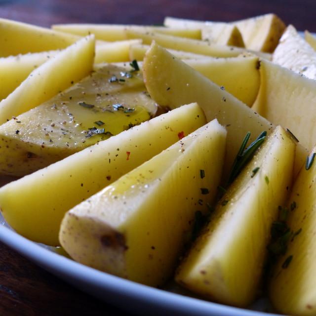 """Raw rosemary potatoes on white plate"" stock image"