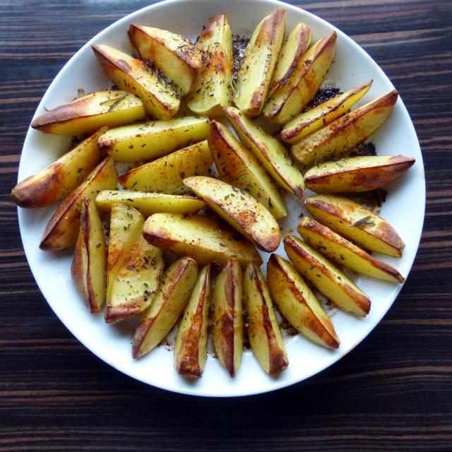 """Prepared rosemary potatoes on white plate"" stock image"