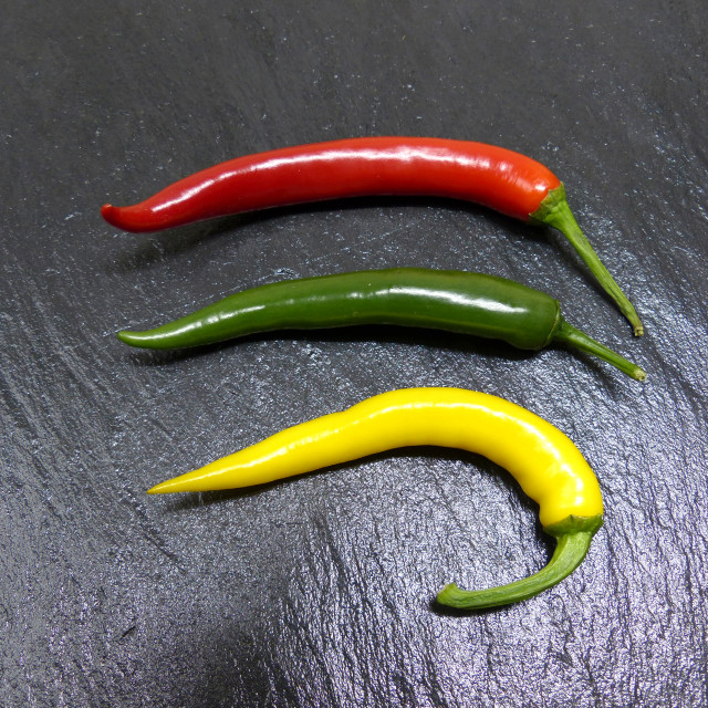 """""""Three chili peppers on a slate"""" stock image"""