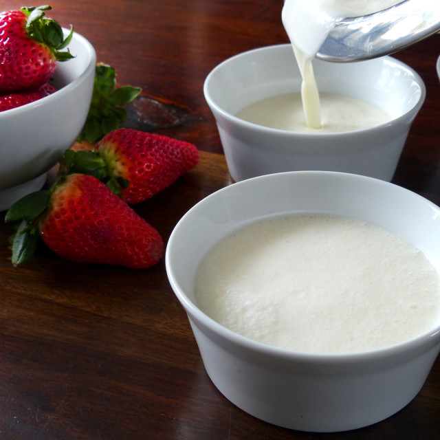 """""""Pouring the panna cotta in small bowls"""" stock image"""