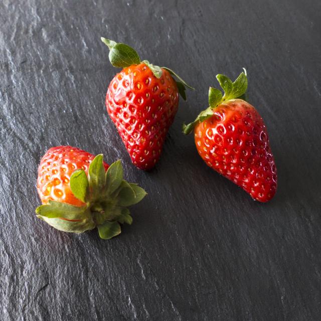 """Three strawberries on a slate"" stock image"