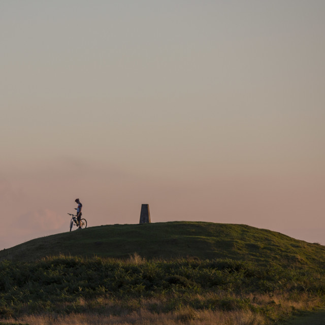 """Sunset cyclist on hill"" stock image"