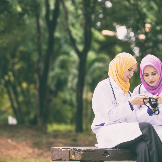 """Asian Doctors in a park with a camera"" stock image"