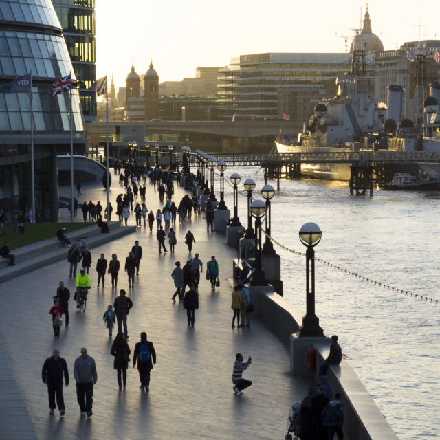 """Pedestrians are silhouetted on More Place riverfront with City Hall and HMS..."" stock image"