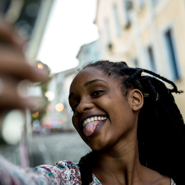 """""""African woman with dreadlocks taking selfie photos in the city"""" stock image"""