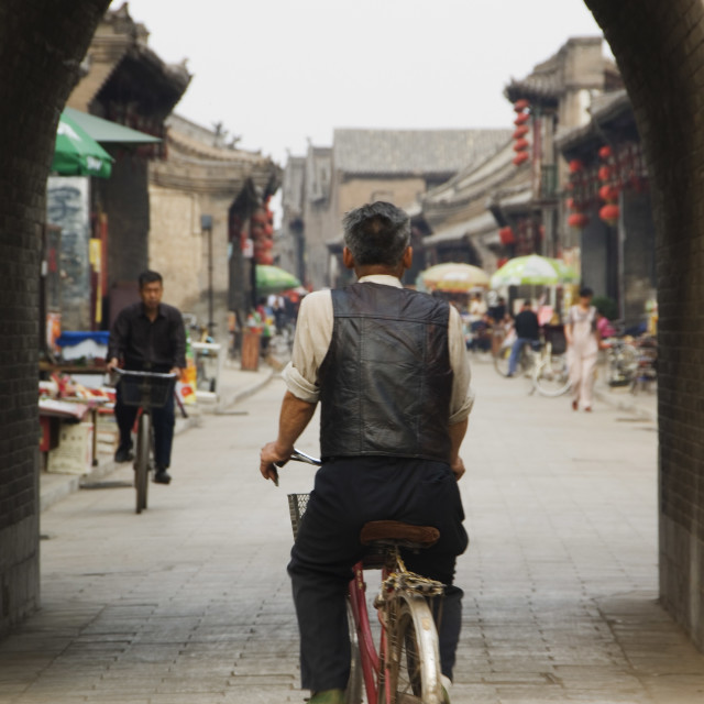 """A man cycling though an arched street in the historic center of Pingyao,..."" stock image"