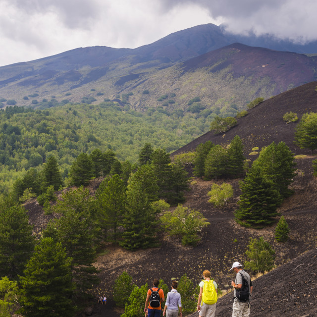 """""""Tourists hiking on an old lava flow from an eruption, Mount Etna, UNESCO..."""" stock image"""