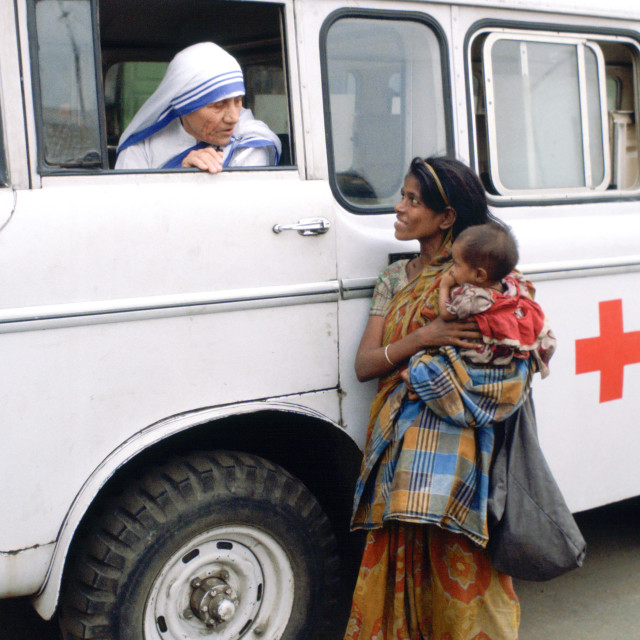 """Mother Teresa talking with a poor woman and her child from a Red Cross..."" stock image"