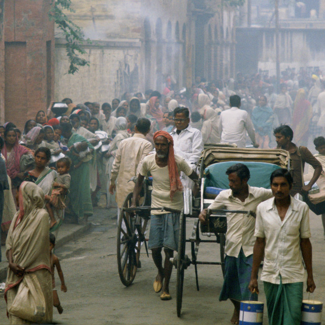 """Rickshaws pass as poor people queue for food in the early morning at Mother..."" stock image"