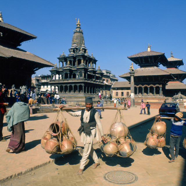"""""""Man and boy carrying heavy pots on shoulder hoists, Patan, Nepal"""" stock image"""