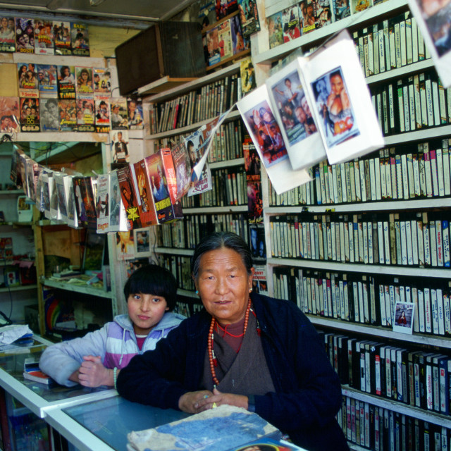 """""""Woman and child in video shop, Paro, Bhutan"""" stock image"""