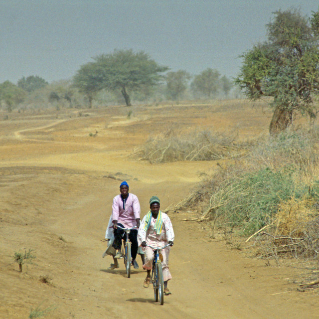 """Two men cycling the deserted road to Sebba, Burkina Faso (formerly Upper Volta)"" stock image"